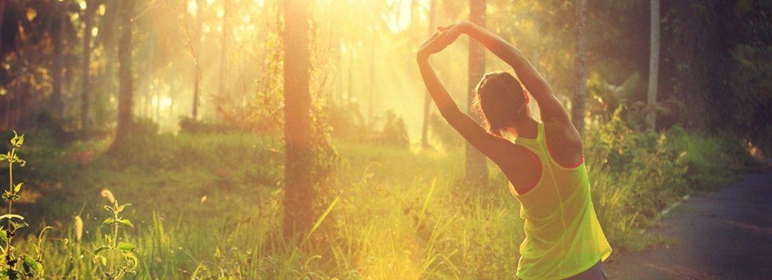 Mulher se alongando em um bosque