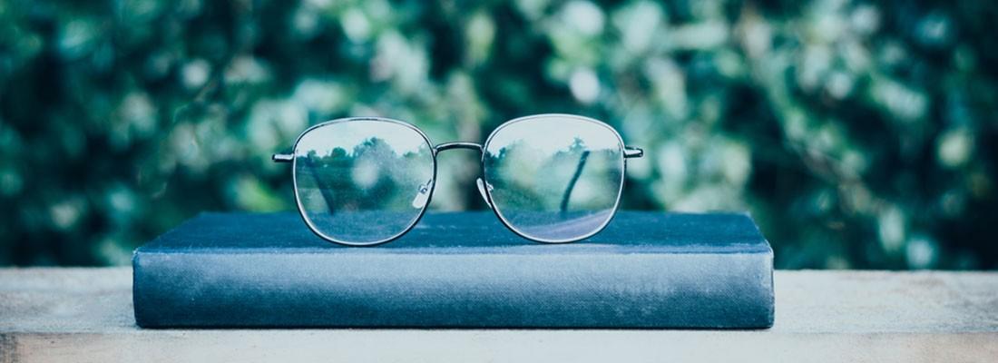 óculos em cima de um livro azul