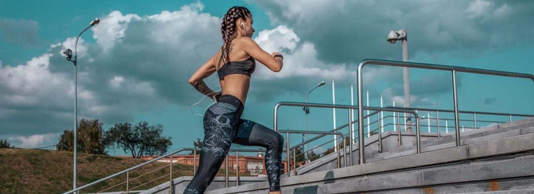 na imagem, mulher correndo subindo escadas com roupas de academia