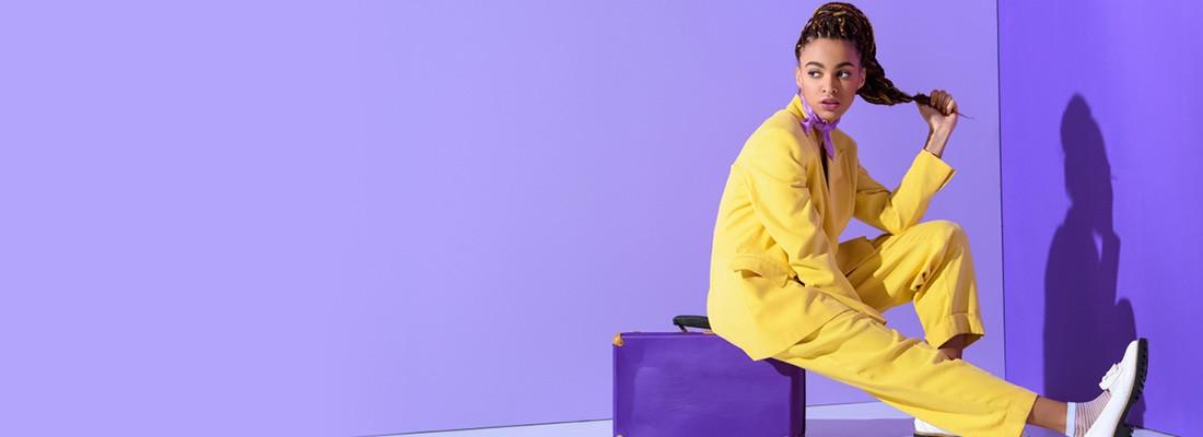 na imagem uma moça sentada de amarelo com um fundo roxo