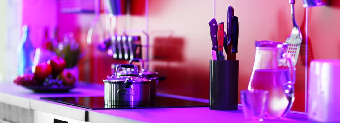 Cozinha com utensilíos e cooktop com tons roxos