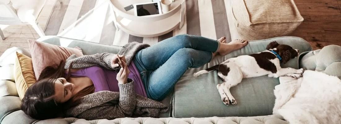 mulher deitada no sofá com cachorrinho e celular na mão