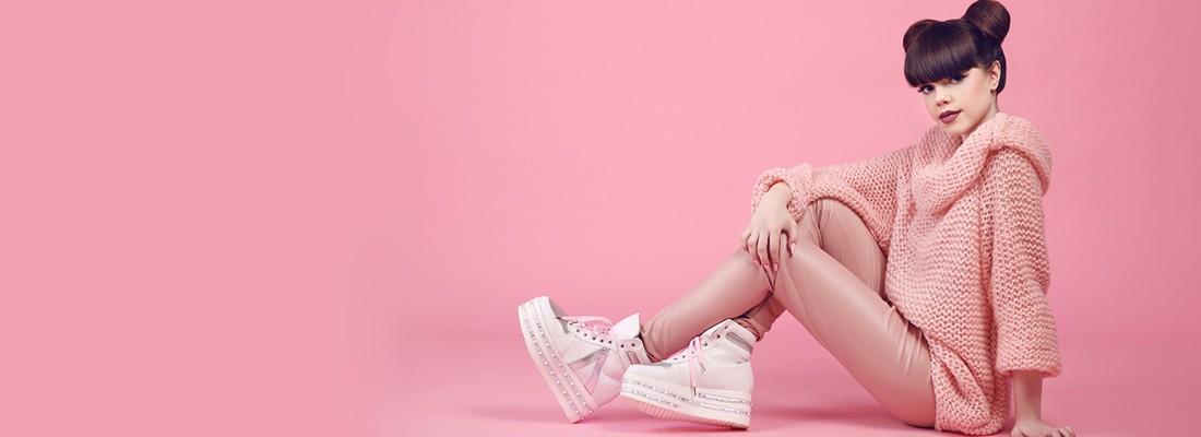 mulher sentada no chão com roupas cor de rosa num fundo também rosa