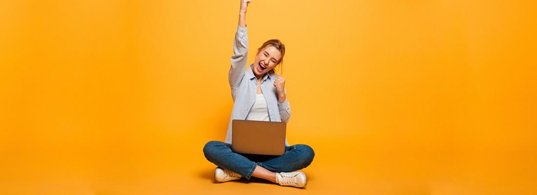 homem sentado na frente do computador sorrindo