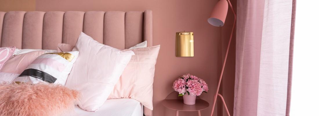 imagem de um quarto com cama e mesa lateral, tudo cor de rosa
