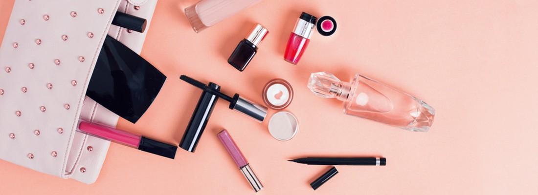 imagem vista de cima com diversos itens de maquiagem e perfumaria