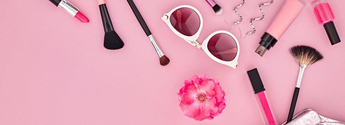imagem vista de cima com diversos itens de maquiagem num fundo cor de rosa