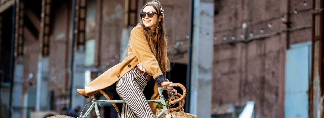 mulher loira usando casaco de mangas compridas amarelas e calça listrada em preto e branco em cima de uma bicicleta e prédio no fundo da imagem.