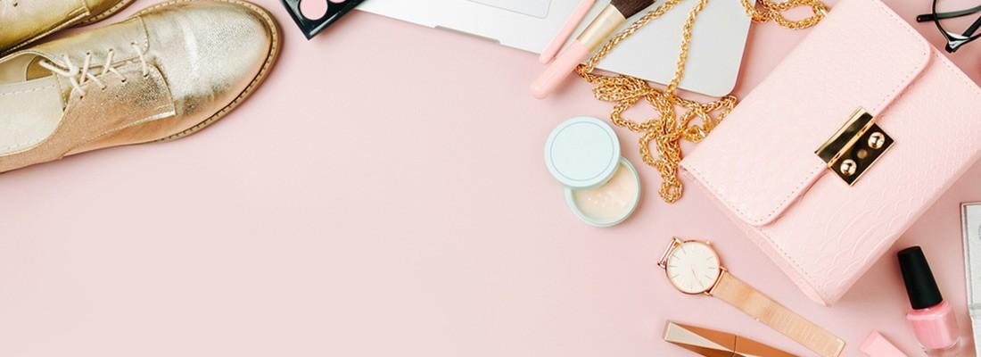 imagem vista de cima com fundo rosa e diversos itens do armário feminino, como tênis, bolsa e maquiagens