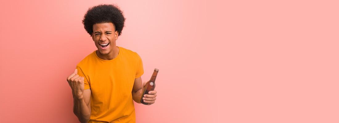 homem de camiseta amarela num fundo rosa segurando uma garrafa na mão com expressão de comemoração